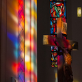 Diekirch, Luxembourg - March 09, 2014: Beautiful colorful sunlight window reflections, a crucifix and a stained glass window in the 19th-century Parish Church of St. Lawrence, St. Laurentius