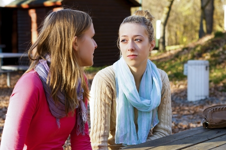 Two beautiful young women talking in the park.